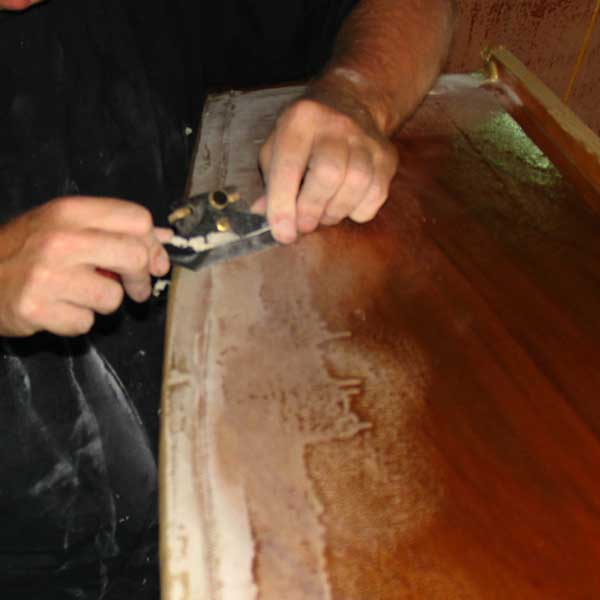 removing edge of glass tape after epoxy has cured with spokeshave: storerboatplans.com